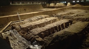 Partially uncovered pit in front, original state covered in back.  All the terracotta warriors were crushed from the collapsed roof and layers of dirt.
